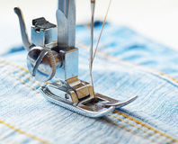 Sewing machine and blue jeans fabric Royalty Free Stock Photos