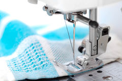 Sewing machine closeup with blue fabric on white. Background Stock Photos