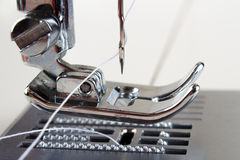 Sewing machine closeup. Presser foot raised with feed dogs Royalty Free Stock Image