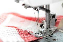 Sewing machine closeup with red fabric on white. Background Royalty Free Stock Photos