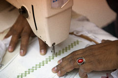 Sewing machine closeup. Two hands holding (adjusting, pushing, feeding) patterned fabric while working with sewing machine also showing tensioner and needle Royalty Free Stock Images