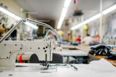 Sewing machine on clothing fabric, nobody. Dressmaking industry, Equipment on dress factory, professional tailoring Stock Image