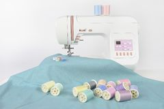 Sewing machine and colorful thread rolls, scissors, fabric and a. Ccessories for sewing on white background, Sewing and needlework concept. Selective Focus Royalty Free Stock Photo