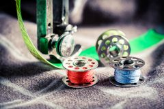 Sewing machine and colorful threads on clothes. Closeup of sewing machine and colorful threads on clothes royalty free stock photo