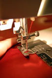 Sewing Machine Detail. With the red thread and cloth and woman's hand Stock Photo