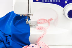 Sewing machine, fabric draped and centimeter on a white backgrou Royalty Free Stock Photos
