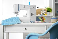 Sewing machine with fabric on table. In tailor workshop royalty free stock photography