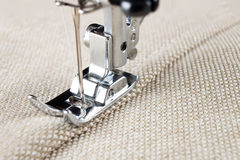 Sewing machine foot and item of clothing Stock Photos