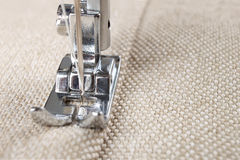 Sewing machine foot and item of clothing. Sewing machine makes a seam on fabric. sewing process royalty free stock image