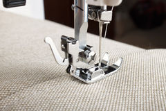 Sewing machine foot and item of clothing. Sewing machine makes a seam on fabric. sewing process royalty free stock photos