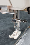 Sewing machine foot and item of clothing. Sewing machine makes a seam on leather. sewing process stock images