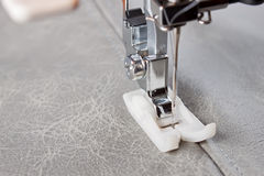 Sewing machine foot and item of clothing. Sewing machine makes a seam on leather. sewing process stock photo