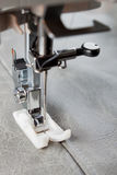 Sewing machine foot and item of clothing. Sewing machine makes a seam on leather. sewing process royalty free stock image