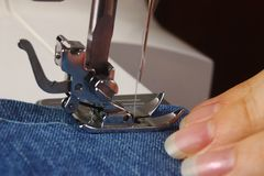 Sewing machine and hand. Closeup detail of a hand operating a sewing machine pressure foot to stitch blue denim fabric royalty free stock photos