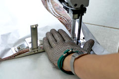 Sewing machine and hand. Closeup detail of a hand operating a sewing machine pressure foot stock images