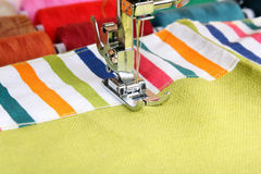 Sewing machine and item of clothing material Stock Photos