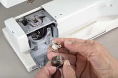 Sewing machine maintenance. A quilter holds the bobbin case and bobbin loaded with thread prior to cleaning the sewing machine Stock Photography