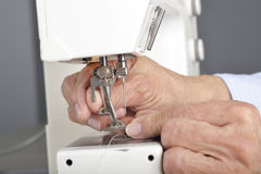 Sewing machine maintenance. A quilter prepares to remove the presser foot and needle in order to clean and maintain a sewing machine Stock Images
