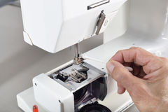 Sewing machine maintenance. A quilter uses a cotton swab to clean the needle holder assembly for routine maintenance Royalty Free Stock Images