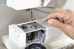 Sewing machine maintenance. A quilter uses a set of twezzers to remove a clump of lint from a sewing machine Royalty Free Stock Image