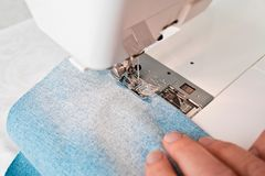 Sewing machine makes zigzag line. On blue cotton royalty free stock photos