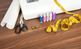 Sewing machine with many utensils on table Royalty Free Stock Image