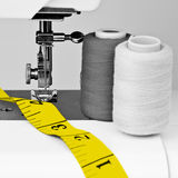 Sewing machine, mesuring tape and reels. Black and white sewing machine and  reels with thread with a contrasting yellow measuring tape Stock Photo