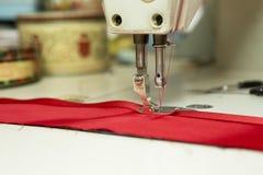 Sewing Machine Needle Binding Red Satin Ribbon to Cloth. Closeup of sewing machine needle stitching red colored cloth to satin ribbon Stock Photography