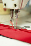 Sewing Machine Needle Fastening Red Cloth and Satin Ribbon. Sewing machine needle fastening satin ribbon to red piece of cloth Royalty Free Stock Photography