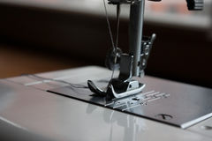Sewing machine needle and sewing accessories. An automatic sewing machine needle in close up Royalty Free Stock Photo