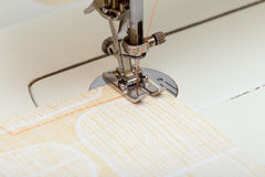 Sewing Machine Needle Stitching Orange Thread on Cloth. Sewing machine stitching orange thread on a piece of cloth Royalty Free Stock Images