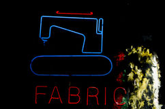 Sewing machine neon. With feather boas in the background Royalty Free Stock Image
