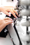 Sewing on a machine. Occupation needlewoman. Seamstress sewing on the sewing machine in the manufacturing plant Royalty Free Stock Photography