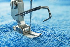 Sewing machine parts call presser foot. Macro image of sewing machine parts call presser foot and needle, on blue towel fabric Stock Image