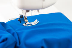 Sewing machine paves the line on blue fabric Stock Photography