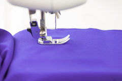 Sewing machine paves the line on the purple fabric Royalty Free Stock Image