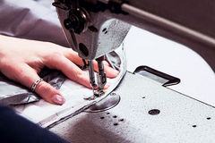 Sewing machine with the processing in progress. Work in progress at the sewing machine royalty free stock image