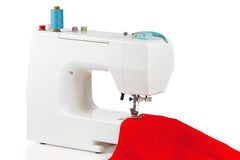 Sewing machine with a red fabric. On a white background Stock Image