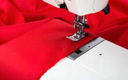 Sewing machine and red fabric isolated on white Royalty Free Stock Photos