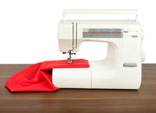Sewing machine and red fabric isolated on white Royalty Free Stock Images