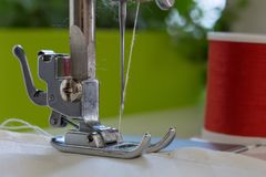 The sewing machine`s foot with a needle sews ecru color  fabric. Close -up.  Stock Image