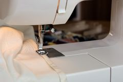 The sewing machine`s foot with a needle sews ecru color  fabric. Sewing machine details.  Stock Photo