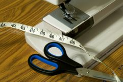 Sewing Machine, Scissors, And Tape Measure. Detail view of sewing machine foot, scissors, and a tape measure Royalty Free Stock Images
