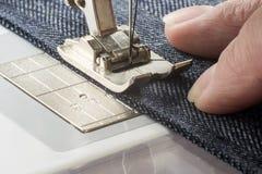 Sewing machine sews denim fabric.  Stock Photos