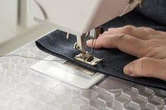 Sewing machine sews denim fabric.  Stock Photo