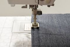 Sewing machine sews denim fabric.  Stock Image
