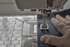 Sewing machine sews denim fabric.  Royalty Free Stock Photography