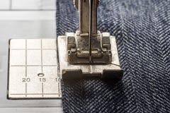 Sewing machine sews denim fabric.  Royalty Free Stock Photo