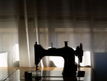Sewing machine silhouette. Behind a window Stock Images