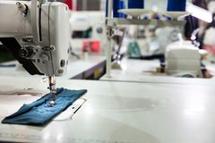 Sewing machine on textile fabric closeup, nobody. Factory production, sew manufacturing, overlock Stock Photos